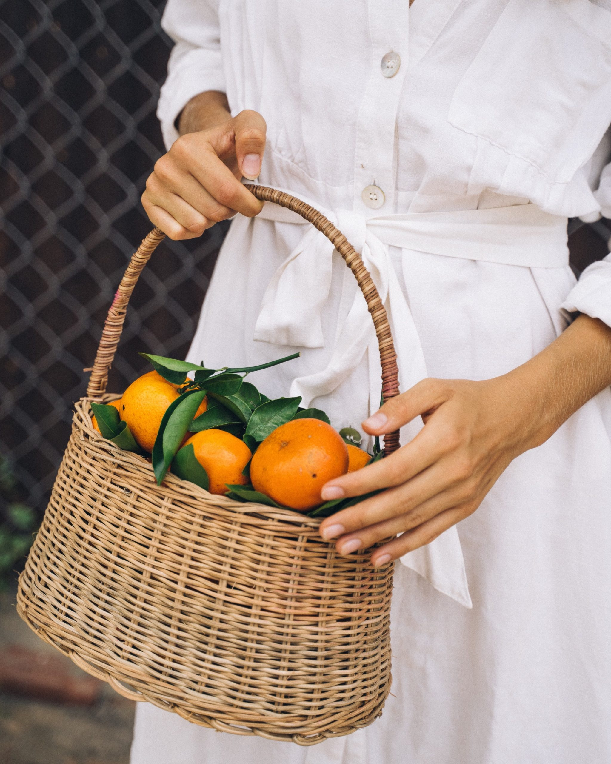Girl in a white dress holding a basket of fruits