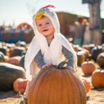 Baby in a costume holding a pumpkin